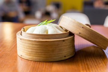 Asian steam bun bao  in a bamboo steamer