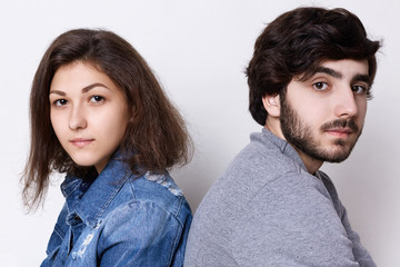 Two young people sitting back to back looking directly into camera. A young couple: brunette girl in jean clothes and stylish bearded man in grey sweater sitting backs relaxing