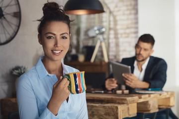 Attractive businesswoman drinking tea