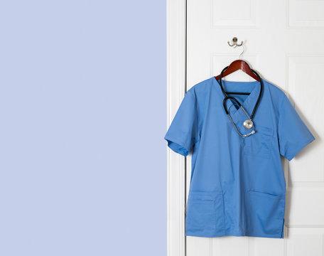 Blue scrubs shirt for medical professional hanging on door
