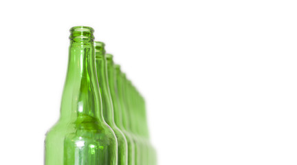 Row of open empty green bottles isolated on white background