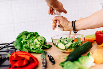 Close up details of a mens hands adding salt and pepper to salad. perfect cook preparing salad for healthy life