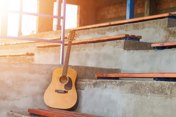 Acoustic guitar leaning on grungy wall. Lens flare