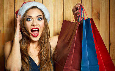 Surprised emotional woman wearing Santa hat holding shopping bag