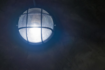 Tungsten wall lamp glowing over dark background.