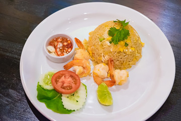 Shrimp Fried Rice in white dish on dark wood table.