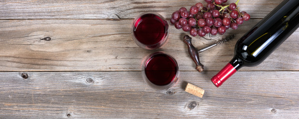 Unopen bottle of red wine and glasses with grapes on rustic wood