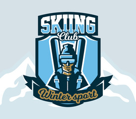 Logo skiing club. Emblem the skier in a cap and ski glasses, backpack and skis. Extreme winter sport. Isolated mountains in the background. Badges shield, lettering. Vector illustration.