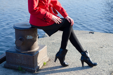 Sexy elegant fashionable lady sitting on the dock column beside river in spring