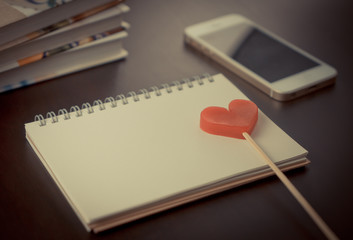 Red heart on blank notebook on working desk with phone