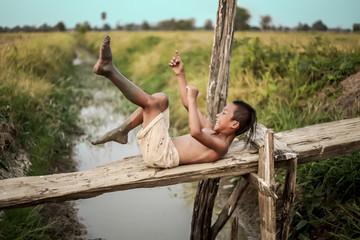 A boy thai ancient hairstyle play in farm,thailand