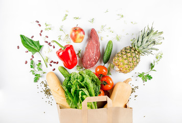 Paper bag full of healthy food on a white background