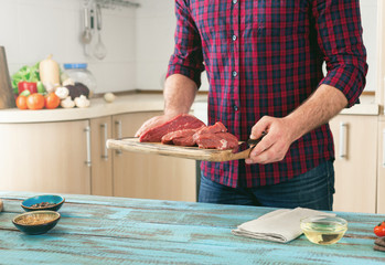 Man cooking meat on wooden table in the home kitchen