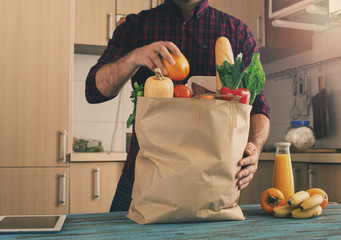 Man examines a paper bag with different healthy food