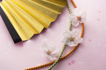 桜の花と金色の扇子と組紐のイメージ