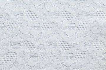 White lace with small flowers on the white background.