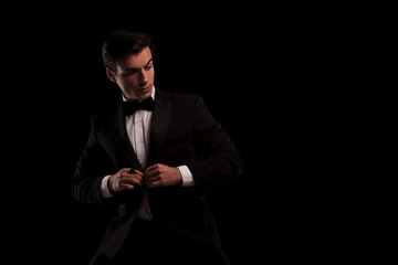 elegant man buttoning his tuxedo and looks to side