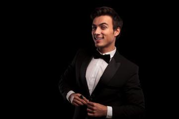 laughing young elegant man buttoning his tuxedo