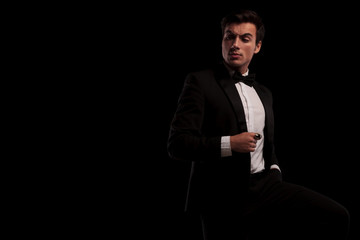 arrogant young man in tuxedo and bowtie looking back