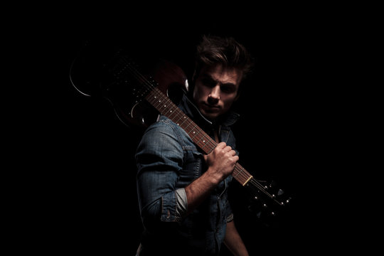 dramatic young guitarist looking back while holding guitar on sh