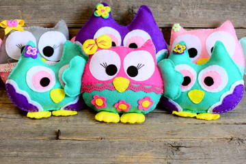 Nice colorful owls toys. Stuffed kids toys on vintage wooden background. Easy crafts made from felt. Simple kids crafts background. Closeup