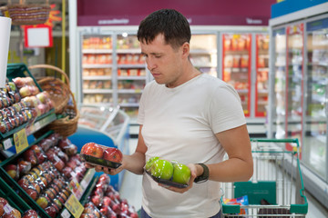 Hard choosing between red and green apples in grocery market. Young caucasian man make his choice in fruit section of supermarket. Comparing of two different goods