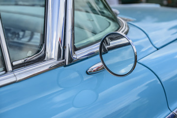 Close up of a mirror on a blue vintage car