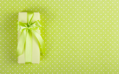 Yellow gift box with a bow on a light green background. Box with surprise on a polka dot background. Copy space.