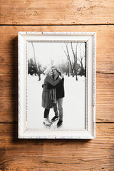 Photo of seniors in picture frame laid on wooden background.