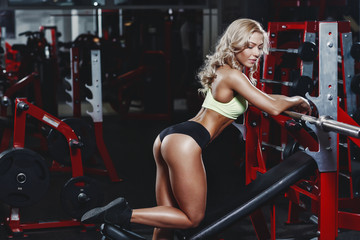 sexy young athletics girl doing biceps barbell curl exercises. Fitness muscled woman in red sport clothing workout with bar in gym