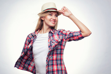 Closeup fashion studio portrait of hipster young smiling woman in white hat and plaid shirt over light blue background