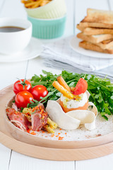 A traditional breakfast with eggs, bacon, cherry tomatoes, baby corn, arugula salad and toast or crisp bread sticks and a cup of coffee