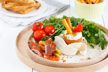 Close-up of a poached egg salad with fresh arugula, bacon, baby corn, cherry tomatoes and toast. European breakfast with eggs Benedict