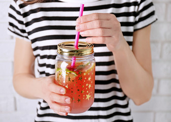 Woman holding fruit lemonade in mason jar, closeup