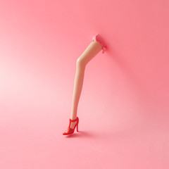 Doll leg on high heels breaking through pastel pink wall. Creati