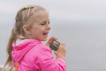Little girl making photo or video at the sunset. Shallow depth of field.