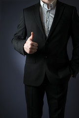 business man in suit showing thumbs up