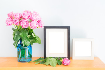 Violet fresh roses with two empty photo frames on wooden shelf