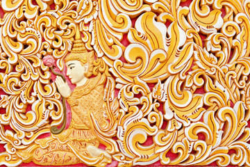 Wall exterior detail of ancient Burmese buddhist temple Dhammikarama in Georgetown on Penang island. Sitting in meditating pose Buddha hold in hand lotus flower. Asian arts, culture. Travel background