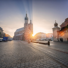 Old town of Krakow with St. Mary's church (Mariacki cathedral) at sunrise, colorful cityscape with rising sun, rays and lens flare, Poland, Europe
