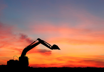 silhouette of Excavator loader at construction site with raised bucket over sunset