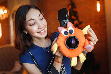 Woman photographer with soft toy on the camera lens to attract child attention