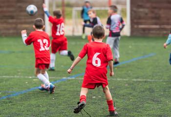 Boys kicking soccer ball at sports field