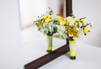 Bright yellow wedding bouquet next to the mirror