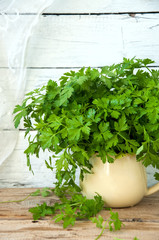 Fresh parsley with water drops in a jar on a wooden table