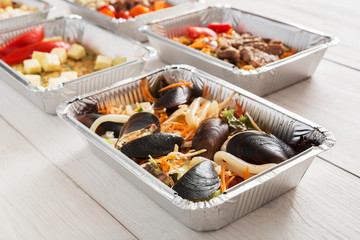 Healthy food take away in foil box at wood background
