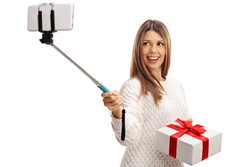 Happy woman holding present and taking selfie with a stick