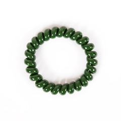Round green spiral elastic band for hair is isolated on a white background