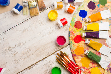 Paints, brushes and palette on the white wood background. The workplace of the artist. Banner for school