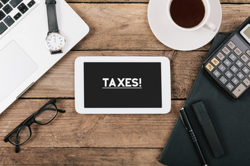 Taxes text on tablet computer on office desk
